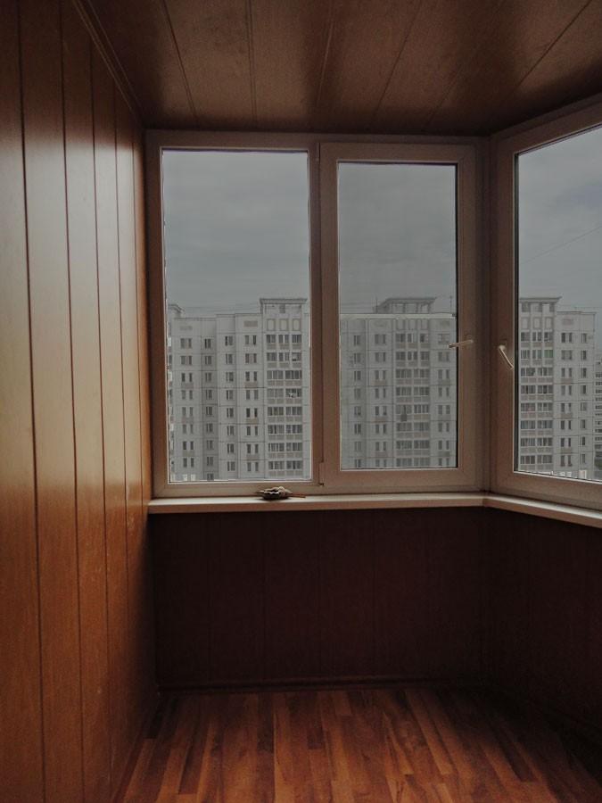 Отделка балкона темным деревом.